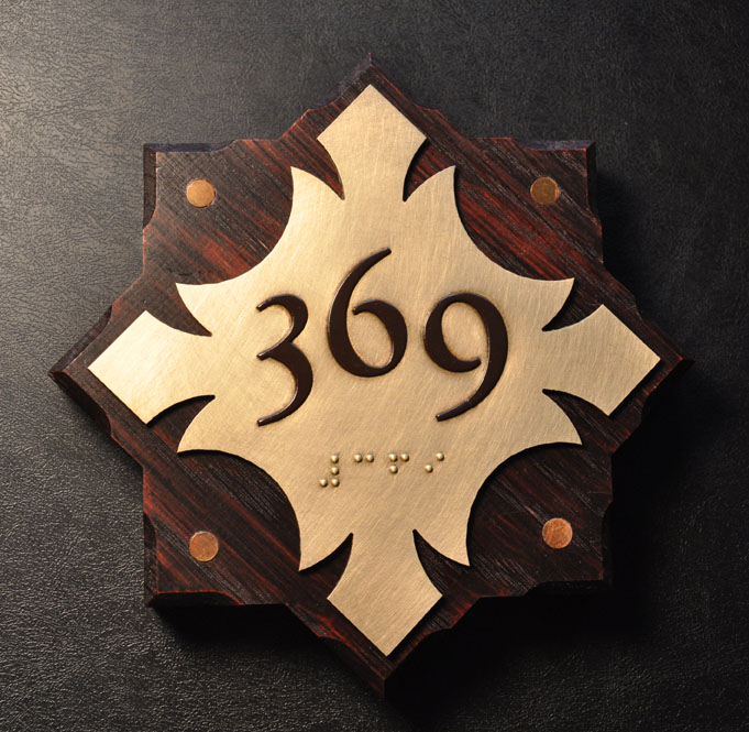 One of nine variations on the guest room sign. There were (3) different brass plates and (3) different stained white oak backers. Edges were stop chamfered. Brass discs were set flush in oak.